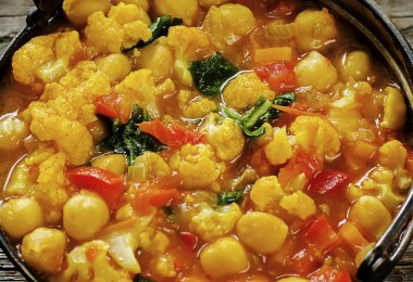 curry chickpea with cauliflower and vegetables on a dark wood background. tinting. selective focus on the middle of curry